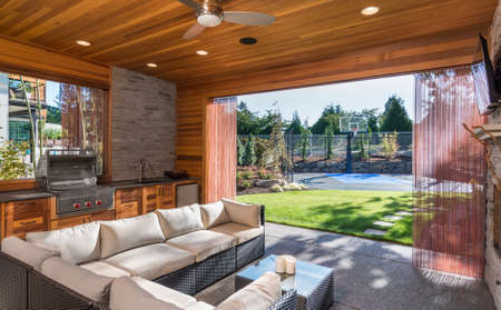 Foto de Beautiful Covered Patio with Barbecue and View of Landscaped Yard and Basketball Court as Part of New Luxury Home - Imagen libre de derechos
