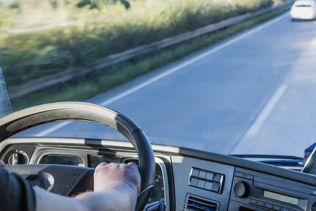 Photo for The driver is holding the steering wheel and is driving a truck on the highway. Free place for your text is in the right side of the photo. All potential trademarks are removed. - Royalty Free Image