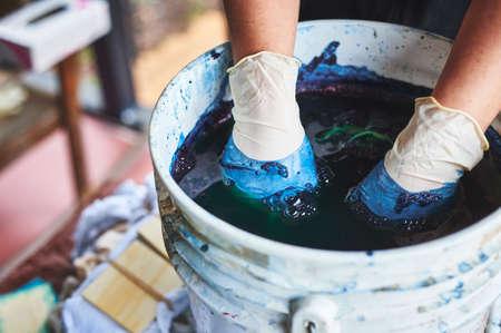 Photo pour a woman dying fabric with indigo dye. - image libre de droit