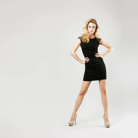 Photo pour Full Length Portrait of a Sexy Blonde Woman in Little Black Fashion Dress - image libre de droit