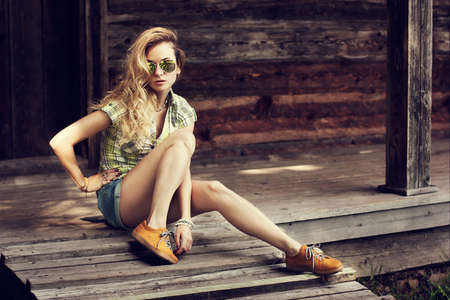 Photo pour Trendy Hipster Girl Sitting on the Wooden Porch. Toned Photo. Modern Youth Lifestyle Concept. - image libre de droit