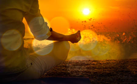 Photo for Woman Practicing Yoga by the Sea at Sunset. Beautiful Toned Photo with Golden Bokeh. Healthy Lifestyle Concept. - Royalty Free Image