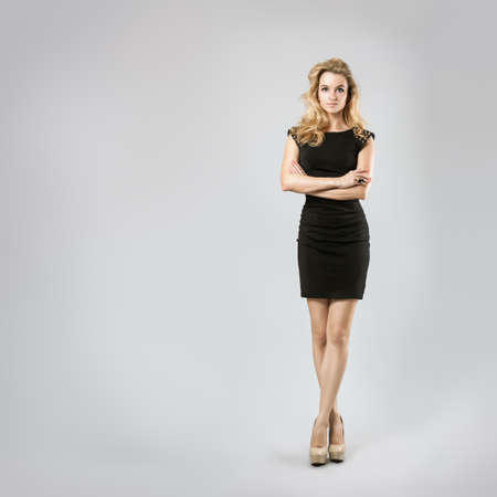 Photo pour Full Length Portrait of a Sexy Blonde Woman in Little Black Dress  Crossed Arms and Legs  Closed Body Posture  Body Language Concept  - image libre de droit