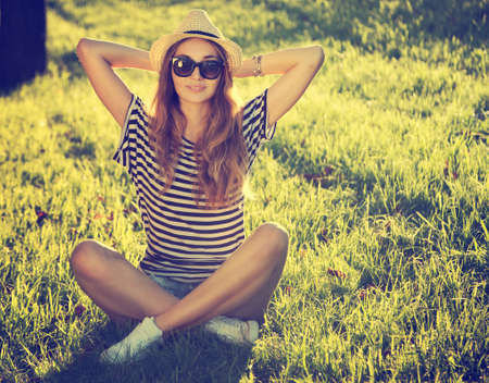 Foto de Trendy Hipster Girl Relaxing on the Grass  Toned and Filtered Photo  Modern Youth Lifestyle Concept  - Imagen libre de derechos