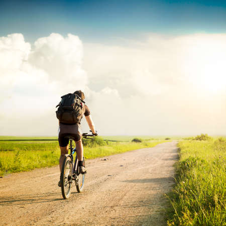 Photo pour Rear View of a Man with Backpack Riding a Bicycle on Beautiful Nature Background. Healthy Lifestyle and Travel Concept.  Styled Toned Photo. Copyspace. - image libre de droit