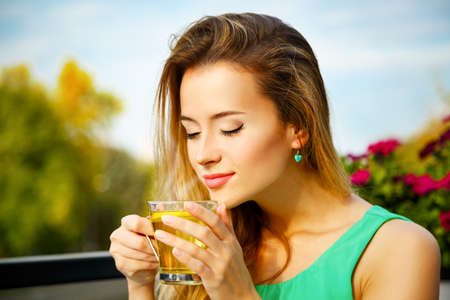 Photo pour Young Woman Drinking Green Tea Outdoors. Summer Background. Shallow Depth of Field. - image libre de droit