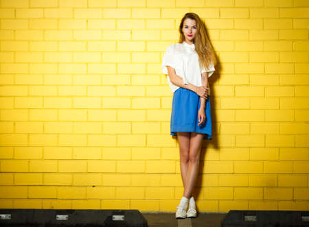 Photo pour Full Length Portrait of Trendy Hipster Girl Standing at the Yellow Brick Wall Background. Urban Fashion Concept. Copy Space. - image libre de droit