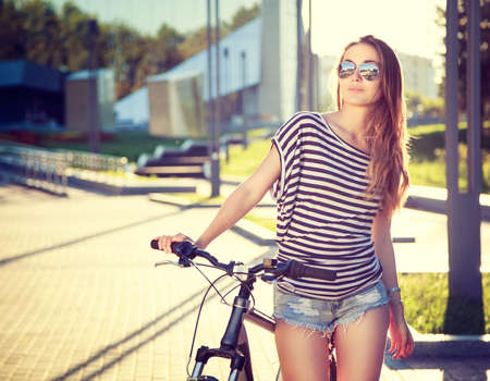 Foto de Trendy Hipster Girl with Bike on Urban Background. Toned and Filtered Photo. Modern Youth Lifestyle Concept. - Imagen libre de derechos