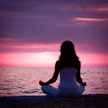 Foto de Silhouette of Woman Meditating in Lotus Position by the Sea at Sunset. Rear View. Nature Meditation Concept.           - Imagen libre de derechos