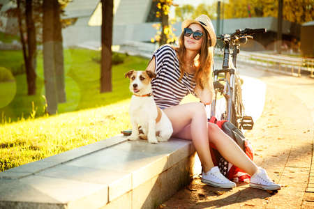 Photo for Smiling Hipster Girl with her Dog and Bike in the City. Toned and Filtered Photo with Bokeh and Copy Space. Urban Youth Lifestyle Concept. - Royalty Free Image