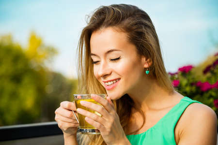 Photo for Young Happy Woman Drinking Green Tea Outdoors. Summer Background. Shallow Depth of Field. Healthy Nutrition Concept. - Royalty Free Image