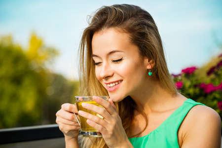Foto de Young Happy Woman Drinking Green Tea Outdoors. Summer Background. Shallow Depth of Field. Healthy Nutrition Concept. - Imagen libre de derechos