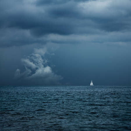 Photo pour Boat Sailing in Center of Storm Formation. Dramatic Background. Danger in Sea Concept. Toned Photo with Copy Space. - image libre de droit