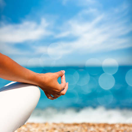 Foto de Yoga Hand on Sea Background. Healthy Lifestyle Concept. Beautiful Photo with Bokeh. Shallow Depth of Field. - Imagen libre de derechos