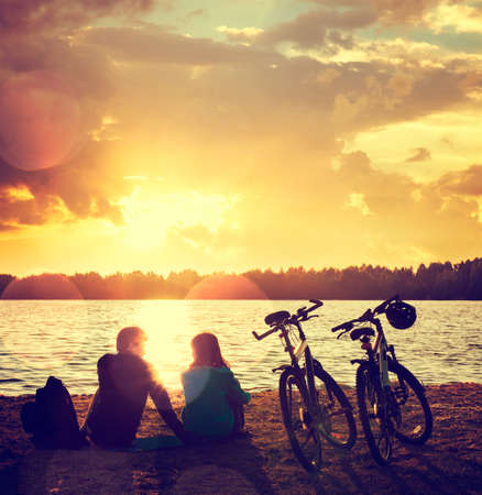 Photo pour Romantic Couple with Bikes Relaxing at Sunset by the Lake. Fall in Love Concept. Toned Photo with Bokeh. - image libre de droit