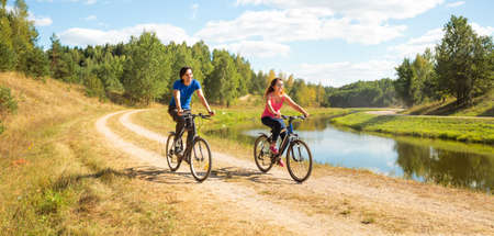 Photo pour Young Happy Couple Riding Bicycles by the River. Healthy Lifestyle Concept. - image libre de droit