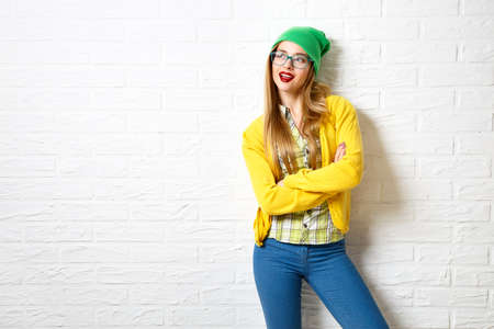 Foto de Street Style Hipster Girl at White Brick Wall Background. Trendy Casual Fashion Outfit in Winter. Copy Space. - Imagen libre de derechos