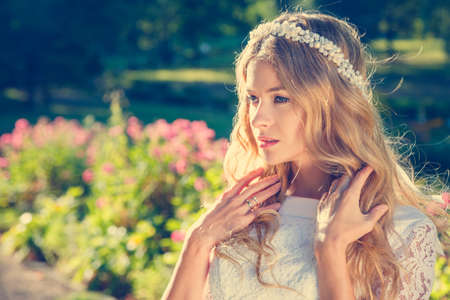 Foto de Charming Bride with Wedding Tiara on Nature Background. Modern Bridal Style. Toned Photo with Copy Space. - Imagen libre de derechos