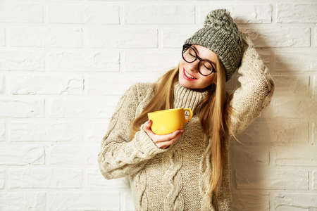 Photo pour Romantic Dreaming Hipster Girl in Knitted Sweater and Beanie Hat with a Mug in Hands at White Brick Wall Background. Winter Warming Up Concept. - image libre de droit