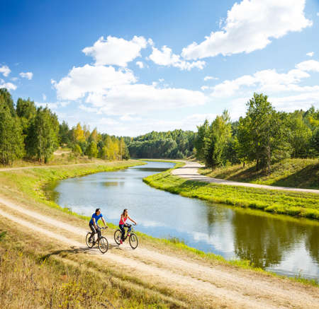 Photo for Young Happy Couple Riding Bicycles by the River. Beautiful Nature Background. Sport Outdoors and Healthy Lifestyle Concept. Copy Space. - Royalty Free Image