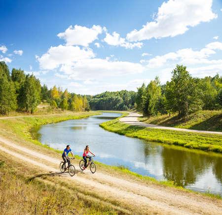 Foto de Young Happy Couple Riding Bicycles by the River. Beautiful Nature Background. Sport Outdoors and Healthy Lifestyle Concept. Copy Space. - Imagen libre de derechos