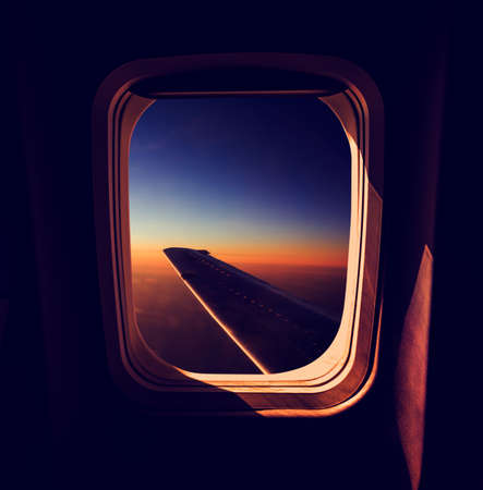 Photo for View from Airplane Window at Sunset. Calm and Sleepy Mood in Air Travel Concept. Dark Atmospheric Toned Photo. - Royalty Free Image