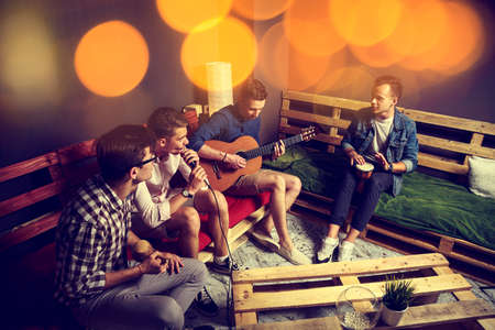 Foto de Group of Four Friends Hanging Out in Studio. Guys Singing and Playing Music in Urban Apartment. Toned Photo with Bokeh. - Imagen libre de derechos