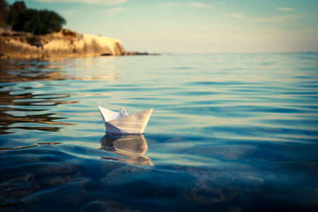 Photo pour Paper Ship Floating in the Sea. Origami Paper Boat Sailing. Beautiful Waves Ripple Background. Unusual Travel Concept. Toned and Filtered Photo with Copy Space. - image libre de droit