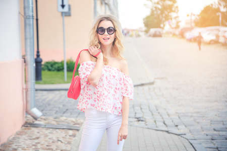 Photo pour Smiling Fashion Woman in the Old Town Street in Europe. Happy Trendy Girl in Round Sunglasses in Summer. Toned Photo with Copy Space and Beautiful Sunlight. - image libre de droit