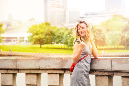 Photo for Happy Smiling Fashion Woman in the City Street. Trendy Girl in Summer. Toned Photo with Bokeh and Copy Space. - Royalty Free Image