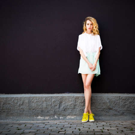 Photo for Full Length Portrait of Trendy Hipster Girl Standing at the Dark Textured Wall Background. Urban Fashion Woman Concept in Summer. Street Style Female. Instagram Styled Toned Photo with Copy Space. - Royalty Free Image