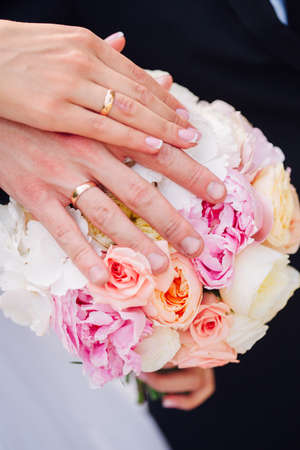 Photo for Hands and rings on wedding bouquet together - Royalty Free Image
