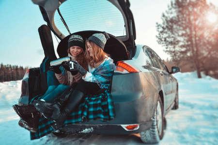 Foto de Happy friends in winter forest in the car. Two happy girls sit in the trunk of a car drinking coffee - Imagen libre de derechos