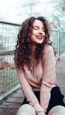 Foto de Fashion portrait of trendy happy young woman sitting near the netting rabitz in the city - Imagen libre de derechos
