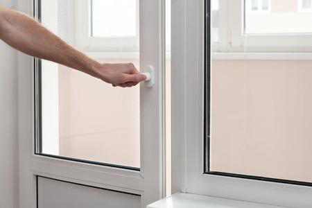 Photo pour The human hand close a plastic vinyl door. - image libre de droit