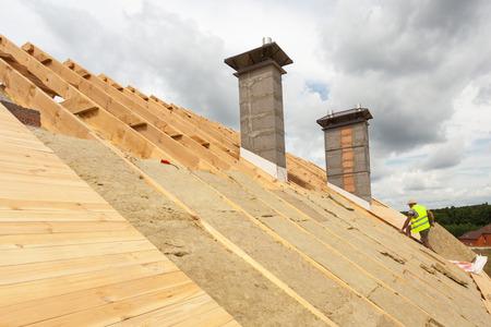 Foto de Roofer builder worker installing roof insulation material (rockwool) on new house under construction - Imagen libre de derechos
