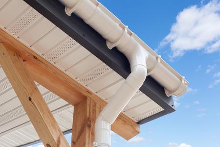 Photo pour SIP panel house construction. New white rain gutter.  Drainage System with Plastic Siding Soffits and Eaves against blue sky - image libre de droit