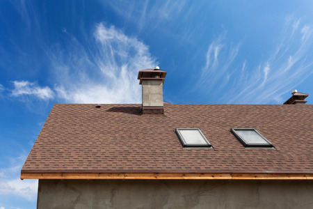 Photo pour New roof with skylight, asphalt roofing (shingles) and chimney. Roof with mansard windows . - image libre de droit