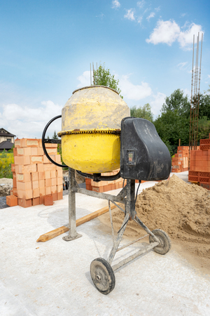 Foto de Construction of brick new home or house. Vertical day lite photo of old yellow professional concentrate mixer stand outside on the foundation of an unfinished building near brick and sand - Imagen libre de derechos