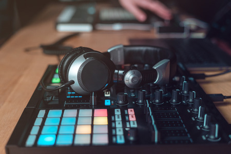 Photo for Photo of earphones on controller or DJ instruments for creative music. Objects lying on wooden table in black modern and sound studio with style interior - Royalty Free Image
