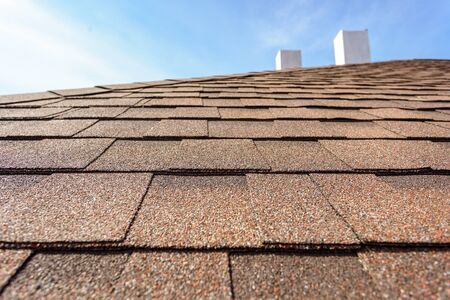 Photo for Close up photo layer of new asphalt shingles on roof top of new house under construction with chimney and blue sky on blurred background - Royalty Free Image