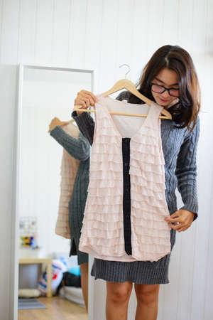 Foto de Asian woman choose dresses in front of a mirror - Imagen libre de derechos