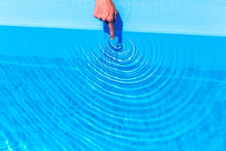 Foto de Forefinger making waves as circles in blue swimming pool - Imagen libre de derechos