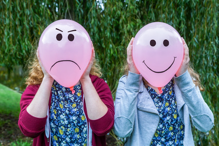 Photo for Two teenage girls holding balloons with smiling and angry facial expressions outdoors - Royalty Free Image