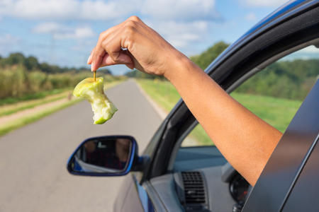 Photo for Female arm throwing  fruit waste out of car window - Royalty Free Image