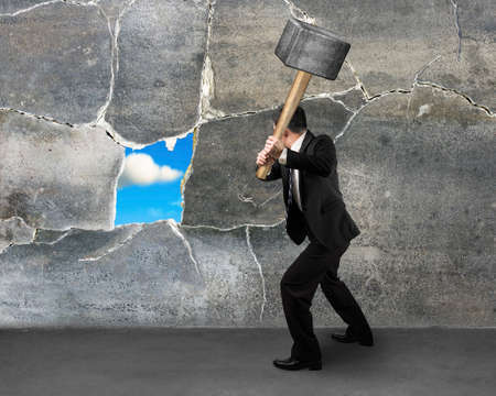 Photo for businessman destructing the wall with a large hammer - Royalty Free Image