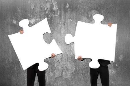 Photo pour Two business people assembling blank white jigsaw puzzles with concrete wall background - image libre de droit