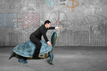 Photo for Businessman riding turtle and indicating with finger in the concrete room and business concept doodles wall background - Royalty Free Image