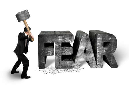 Photo pour Businessman holding sledgehammer hitting 3d fear mottled concrete word isolated on white background, overcoming fear concept. - image libre de droit