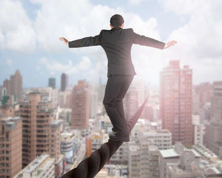 Photo pour Businessman balancing on a wire with sky clouds cityscape background. - image libre de droit